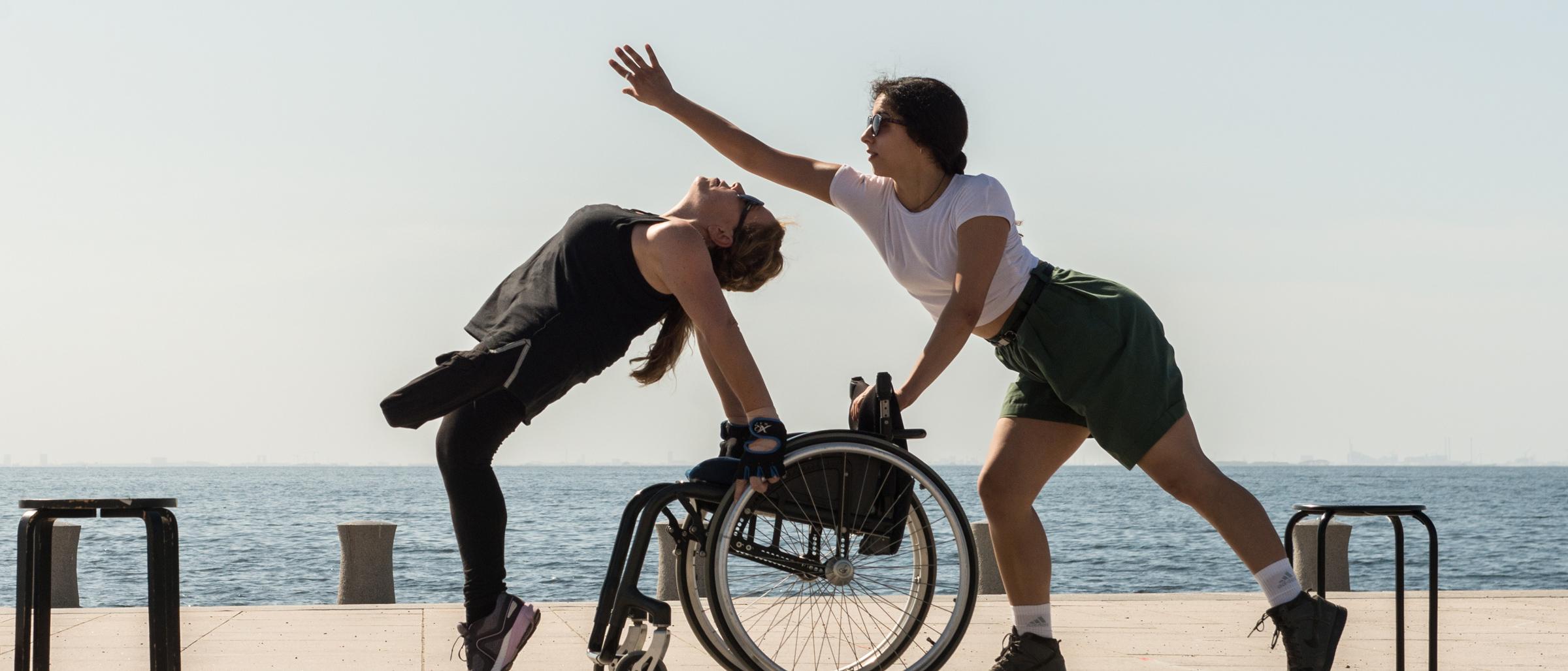 Två dansare och en rullstol dansar i solen framför Öresund i föreställningen Cherry-Picked, foto: Jenny Baumgartner