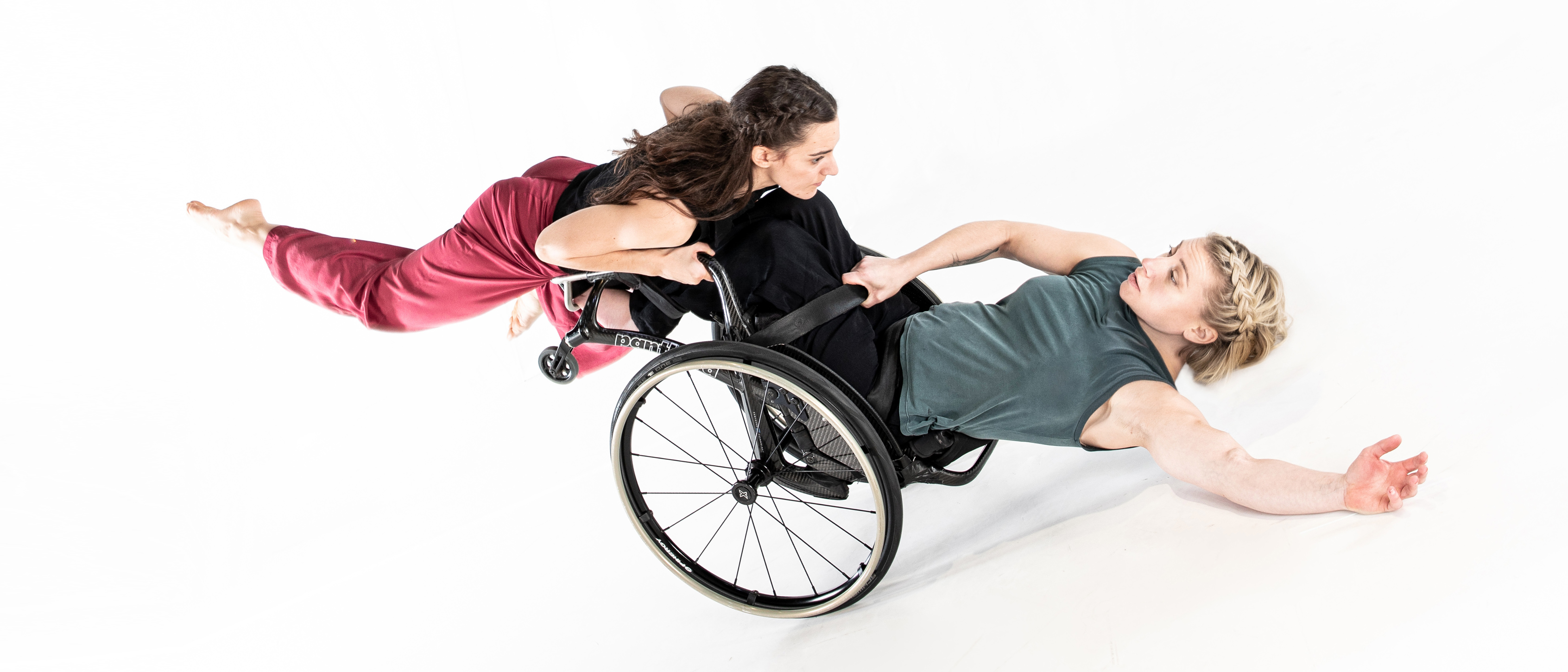 Dancer Anna is holding onto the sides of a wheelchair in which dancer Madeleine is sitting. The wheelchair is leaning backwards with Madeleine stretching her hand forward as Anna runs while holding her.