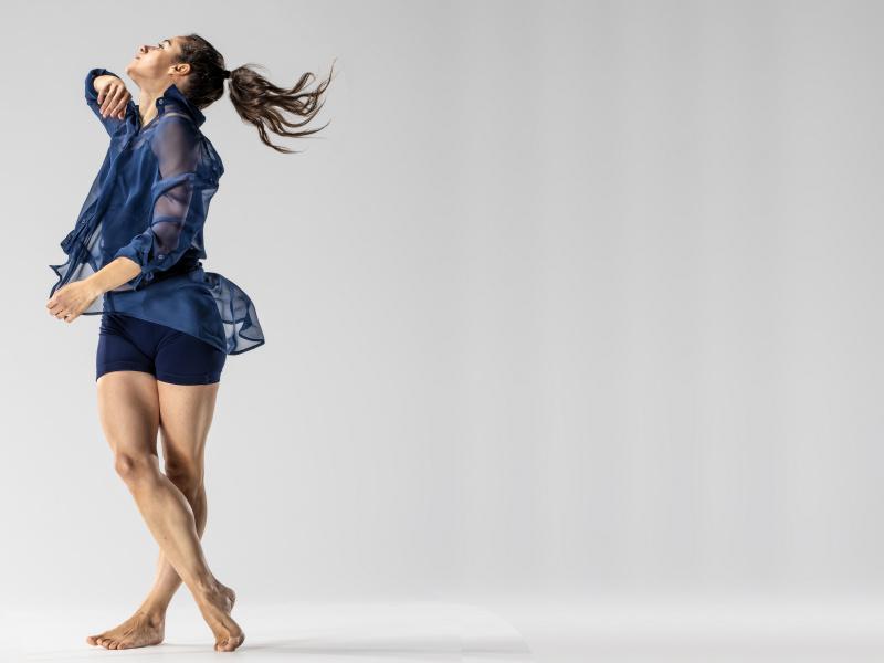 DAnsare Marion Rastouil korsar sende sina ben och rör sig i en snurrande rörelse med armarna böjda. Foto: Håkan Larsson.
