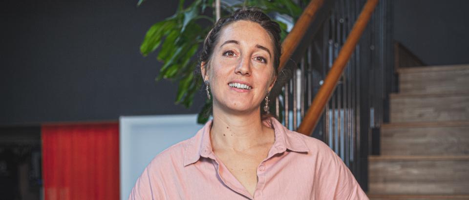 Projektledaren Celine Orman står i en trappa på Skånes Dansteater. Hon bär en rosa skjorta, har uppsatt brunt hår och bruna ögon.