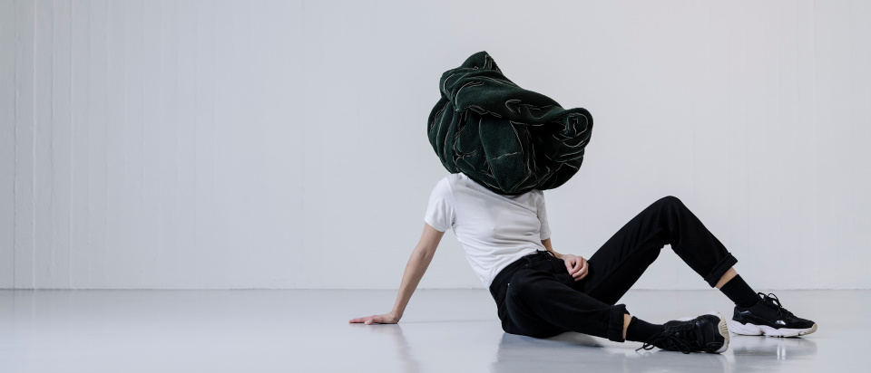 En kvinna i vit t-shirt, svarta jeans och sneakers sitter på golvet, lutar sig bakåt med en hand i golvet. Över hennes huvud har hon ett ihopknycklad mörkgrått lurvigt tyg som blir till en skulpural form.