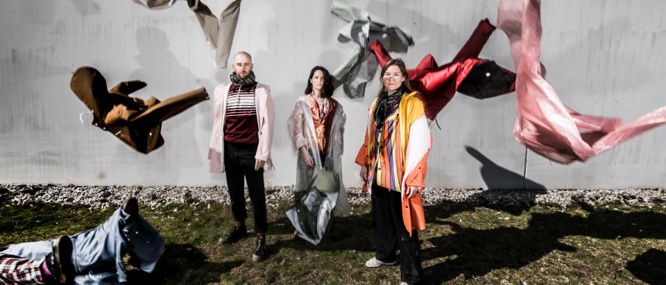 Tre dansare står på en ojämn gräsmatta framför en grå betongvägg. Dansarna har på sig flera lager av dovt färgade och mönstrade kläder. I luften runtomkring dansarna flyger olika klädesplagg runt i luften.