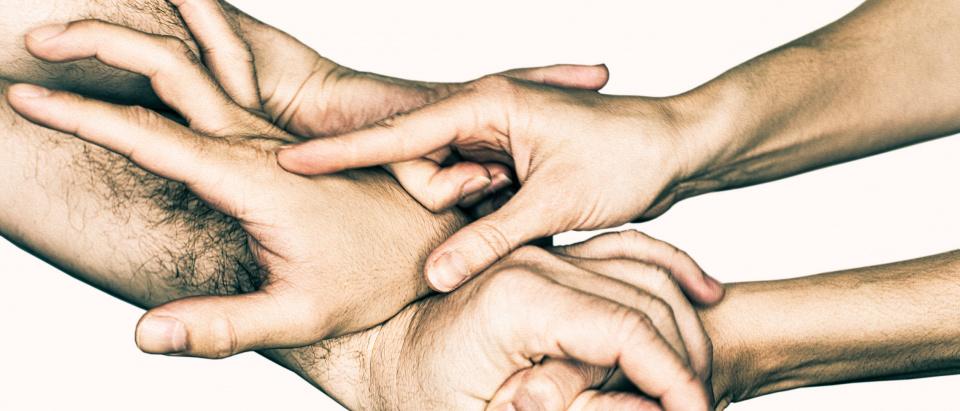 Fem händer sammanflätas om varandra.