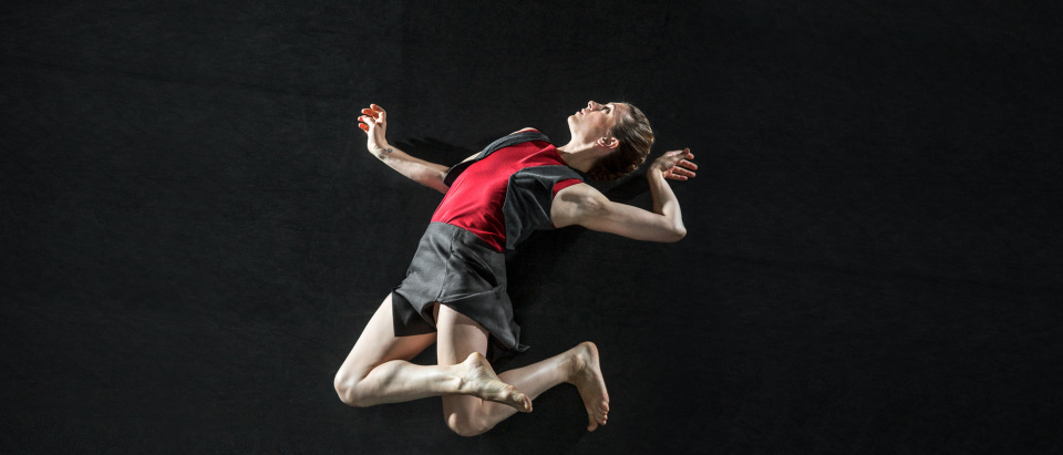 Skånes Dansteaters dansare Sarah Bellugi Klima ser ut att svävca i luften med armar och ben vända i annorlunda vinklar.