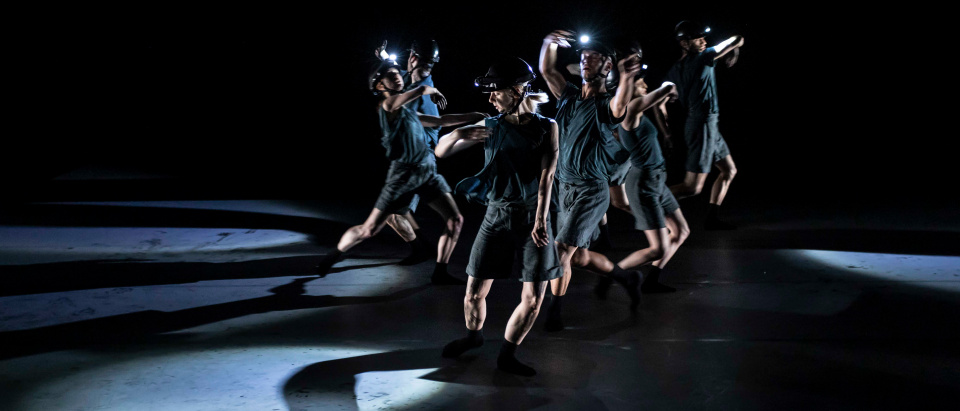 Föreställningsbild ur Skånes Dansteaters föreställning Burnt Offering av Hyerim Jang. Dansare dansar med svängande armar i mörkgrå kläder med bygghjälmar och ficklampor på huvudet.