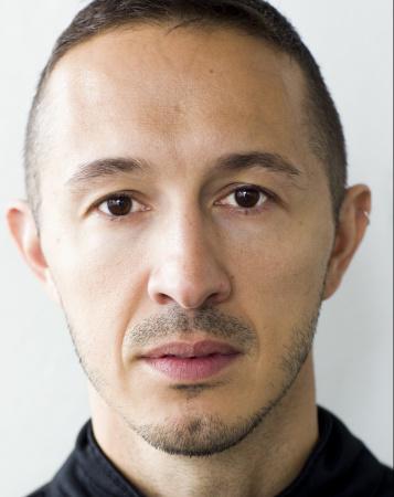 Koreografen Fabio Liberti med svart skjorta, med bruna ögon, snaggat kort hår som är lite längre uppe på huvudet och kort skäggstubb tittar på dig.